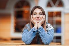 Chiuda sul ritratto di bella seduta bionda del fronte della magra della mano della ragazza all'aperto in caffè accogliente in cit immagine stock libera da diritti