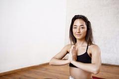 Chiuda sul ritratto di giovane bella ragazza atletica che pratica l'yoga dell'interno con le palme nel gesto del namaste che guar immagine stock libera da diritti