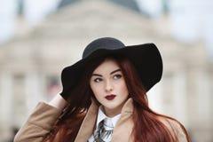Chiuda sul ritratto di giovane bella signora che indossa i vestiti classici alla moda che posano sulla via Ragazza che guarda da  fotografia stock