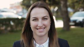 Chiuda sul ritratto di giovane bello sorridere della donna di affari all'aperto archivi video