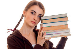 Chiuda sul ritratto di giovane ragazza attraente dello studente in vestiti marroni di sport con molti libri in mani isolate su bi Fotografia Stock Libera da Diritti
