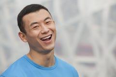 Chiuda sul ritratto di giovane uomo atletico sorridente in una maglietta blu all'aperto a Pechino, Cina Immagini Stock