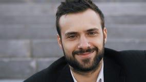 Chiuda sul ritratto di giovane uomo d'affari barbuto che sorride e che esamina la macchina fotografica in via all'aperto fotografie stock libere da diritti