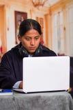 Chiuda sul ritratto di giovane uomo latino indigeno che per mezzo del computer portatile fotografia stock