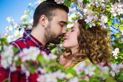 Chiuda sul ritratto di giovani belle coppie che baciano nella fioritura Fotografia Stock