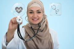 Chiuda sul ritratto di medico femminile arabo che sorride mentre per mezzo dello stetoscopio Immagini Stock