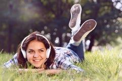Chiuda sul ritratto di musica d'ascolto della ragazza graziosa che si trova all'erba Immagini Stock Libere da Diritti