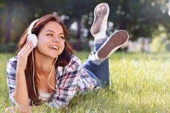 Chiuda sul ritratto di musica d'ascolto della ragazza graziosa che si trova all'erba Fotografie Stock