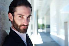 Chiuda sul ritratto di un modello di moda maschio serio con la barba Fotografia Stock