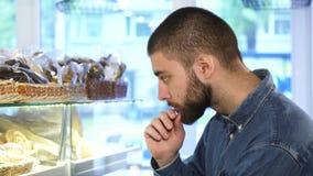 Chiuda sul ritratto di un uomo bello che sceglie i dessert dalla vetrina immagine stock libera da diritti