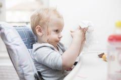Chiuda sul ritratto di una bambina di due anni che mangiano la barra di cioccolato e del fronte coperto in cioccolato Fotografia Stock