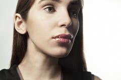 Chiuda sul ritratto di una giovane donna con pelle fresca pulita, colori scuri Fotografia Stock