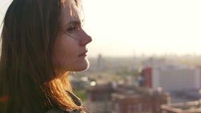Chiuda sul ritratto di una ragazza che sta sul tetto e goda della vista della città Movimento lento archivi video