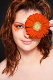Chiuda sul ritratto grazioso della ragazza con il fiore Fotografia Stock