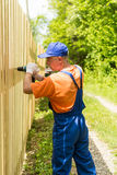 Chiuda sul ritratto nel del tuttofare esperto che monta il recinto del bordo di legno Immagini Stock