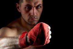 Chiuda sul ritratto scuro di un combattente muscolare aggressivo, mostrante il suo pugno su fondo scuro, fuoco selettivo immagini stock