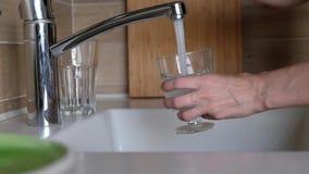 Chiuda sul rubinetto di acqua femminile di apertura della mano e sull'acqua di versamento in vetro sulla cucina video d archivio