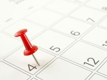 Chiuda sul singolo perno rosso di spinta fissato sul quarto luglio alla pagina del calendario da scrivania Fotografia Stock