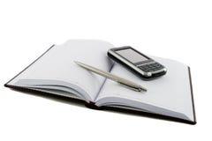 Chiuda sul taccuino, sulla penna e sul telefono mobile Immagini Stock