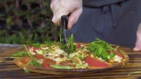 Chiuda sul taglio della pizza sulle fette con il coltello del rullo sulla tavola di legno in pizzeria Cuoco del cuoco unico che a video d archivio