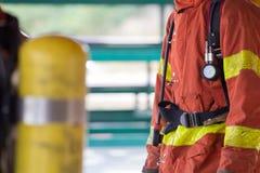 Chiuda sul vigile del fuoco in vestito ed attrezzatura della protezione di estinzione di incendio Fotografia Stock