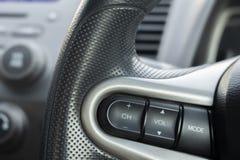Chiuda sul volante con il primo piano dei bottoni di controllo Controllo di sistema stereo dell'automobile immagini stock