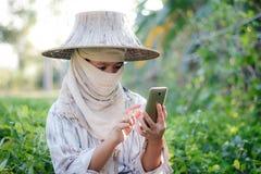 Chiuda sull'agricoltore del colpo che utilizza lo smartphone mobile nell'azienda agricola della natura Fotografie Stock