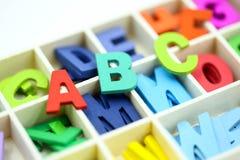 Chiuda sull'alfabeto inglese di legno variopinto su fondo bianco Immagine Stock