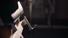 Chiuda sull'esercizio con il bilanciere per il bicipite nella palestra 4k video d archivio