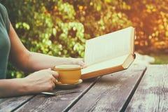 Chiuda sull'immagine del libro di lettura della donna all'aperto, accanto alla tavola ed alla tazza di legno del coffe al pomerig Fotografia Stock