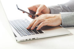 Chiuda sull'immagine dell'uomo a funzioni multiple di affari che per mezzo di un computer portatile e di un telefono cellulare Fotografie Stock