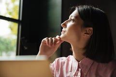 Chiuda sull'immagine della donna pensierosa che si siede dalla tavola Immagini Stock