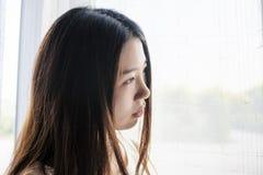 Chiuda sull'immagine della ragazza nella finestra immagini stock libere da diritti
