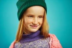 Chiuda sull'immagine della ragazza sveglia in maglione e cappello dell'inverno sul blu immagini stock
