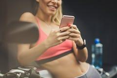Chiuda sull'immagine di giovani donne sorridenti felici di sport che usando la p astuta fotografie stock libere da diritti