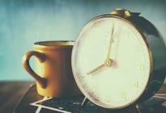 Chiuda sull'immagine di vecchi orologio e tazza di cofee sopra la tavola di legno l'immagine è filtrata con retro stile sbiadito Fotografia Stock Libera da Diritti