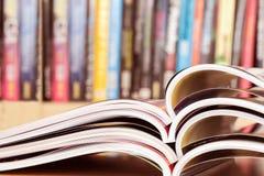 chiuda sull'impilamento della rivista aperta con il backg confuso dello scaffale per libri immagine stock