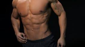 Chiuda sull'uomo che mostra il suo torso muscolare video d archivio
