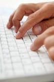 Chiuda sull'uomo che per mezzo della tastiera di calcolatore Fotografie Stock Libere da Diritti