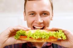 Chiuda sull'uomo che prende il morso del panino Fotografie Stock