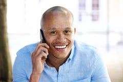 Chiuda sull'uomo d'affari africano sorridente che parla sul cellulare Immagine Stock