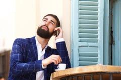 Chiuda sull'uomo d'affari serio che si siede al caffè con caffè che parla sul cellulare Fotografie Stock Libere da Diritti
