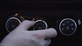 Chiuda sull'uomo del colpo la mano del ` s che accende il sistema di condizionamento d'aria nella macchina video d archivio