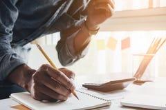Chiuda sull'uomo del ragioniere che per mezzo del calcolatore mentre scrivono faccia la nota Fotografia Stock Libera da Diritti