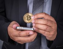 Chiuda sull'uomo di affari con bitcoin e telefono cellulare usando Immagine Stock Libera da Diritti