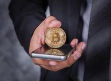 Chiuda sull'uomo di affari con bitcoin e telefono cellulare usando Fotografia Stock Libera da Diritti