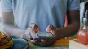 Chiuda sull'uomo di colore irriconoscibile che manda un sms sullo smartphone al tempo del pranzo in self-service video d archivio