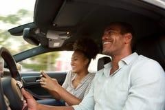 Chiuda sull'uomo e sulla donna afroamericani sorridenti nel sorridere dell'automobile fotografia stock libera da diritti