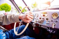 Chiuda sull'uomo irriconoscibile che conduce un'automobile del veterano Fotografia Stock Libera da Diritti