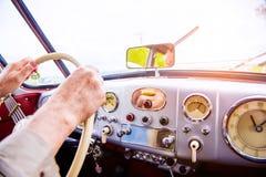 Chiuda sull'uomo irriconoscibile che conduce un'automobile del veterano Fotografia Stock